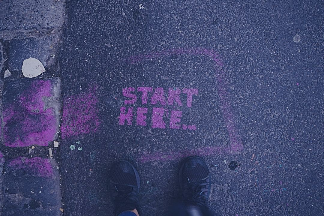 """Person standing on street in front of the words """"start here"""" written in pink chalk"""