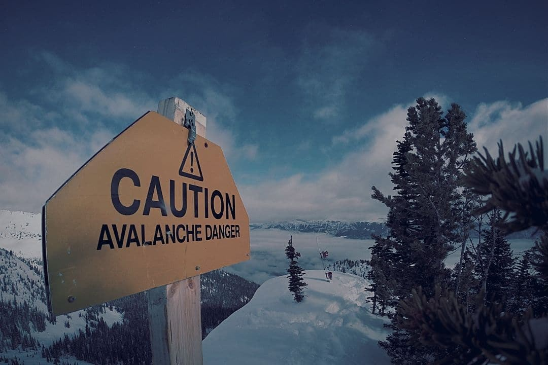 caution sign on snowy mountain